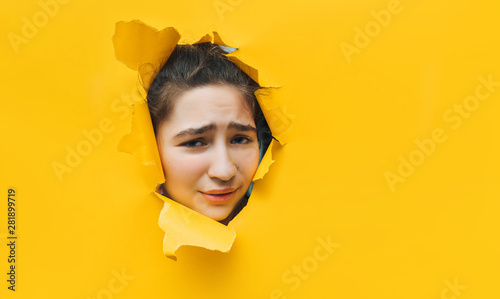 Fényképezés  What? Funny angry teenage girl peeping through hole on yellow paper