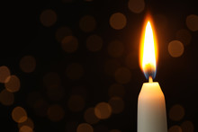 Burning Candle On Black Background With Blurred Lights, Space For Text