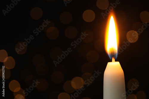 Fotografia  Burning candle on black background with blurred lights, space for text