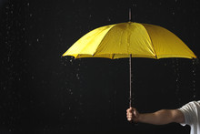 Man Holding Yellow Umbrella Under Rain Against Black Background, Closeup