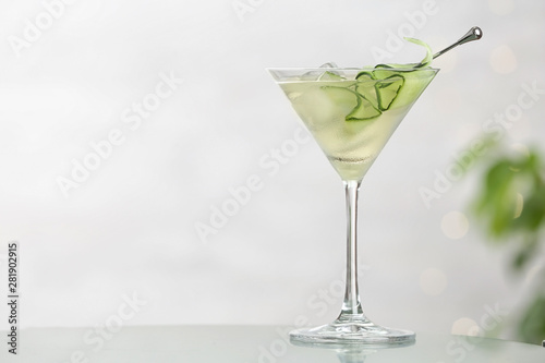 Fotografía Glass of tasty cucumber martini on table against light background, space for tex