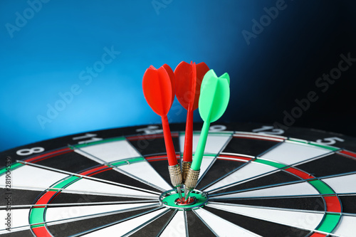 Canvas Prints Countryside Arrows hitting target on dart board against blue background