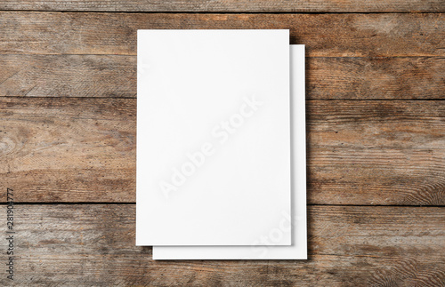 Fototapeta Stack of blank paper sheets for brochure on wooden background, top view. Mock up obraz