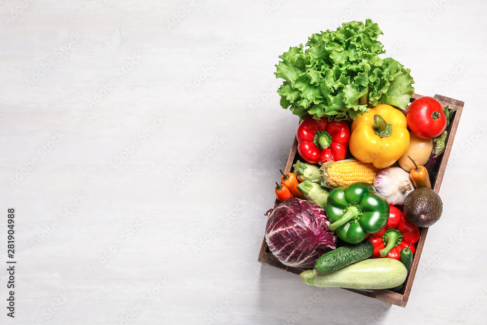 Fototapeta Crate with different fresh vegetables on light background, top view. Space for text