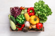 Crate with different fresh vegetables on light background, top view
