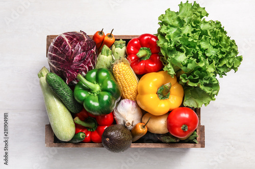 Poster Cuisine Crate with different fresh vegetables on light background, top view