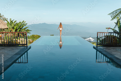 Fotografia  Slim young woman in swimsuit relaxing on edge tropical infinity pool in mountains