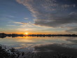 Panorama Lake view morning of fat clouds moving above reservoir and reflection in water with yellow sun light in the sky background, sunrise at Krajub reservoir, Ban Pong, Ratchaburi, Thailand.