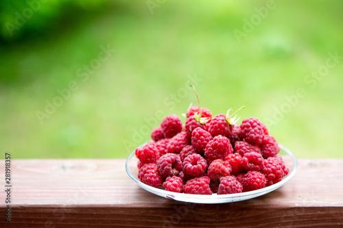 Fototapeta Raspberry berries on a wooden table. Summer mood. A treat. Green background. obraz na płótnie
