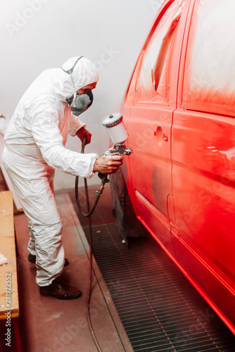 Details of industrial worker, mechanic engineer painter painting a car using a c Canvas Print