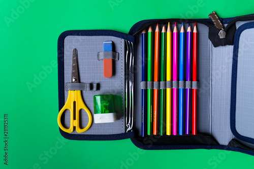 Cuadros en Lienzo Pencil case with school supplies on a green paper background with copy space