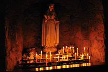Altar With Lit Candles In A Catholic Church. The Figure Of The Holy Virgin Mary.