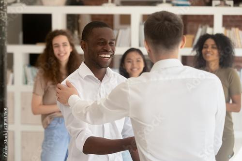 Cuadros en Lienzo  Diverse company head shake hands african employee during reward