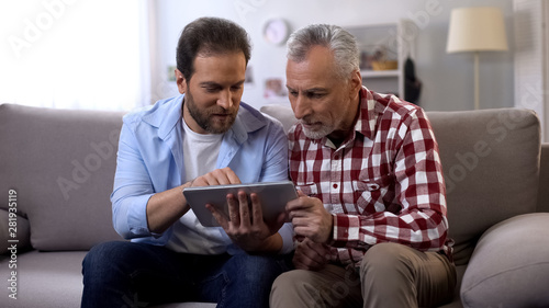 Retiree father and middle aged son scrolling tab, watching photos from vacation Canvas Print