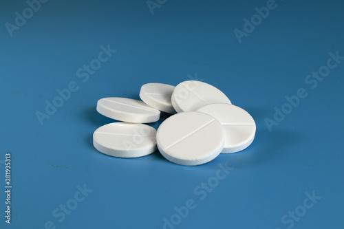 Fototapeta White big pills on a blue background. obraz na płótnie