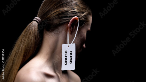 Lady with dumb blonde tag on ear against dark background, humiliation stereotype Wallpaper Mural