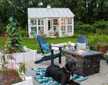 Beautiful Garden With Lit Firepit, Andirondack Chairs Greeenhouse With Great Dane Dog Lying On Blanket In Foreground