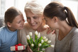 Attentive grown up daughter and granddaughter congratulating grandmother with birthday