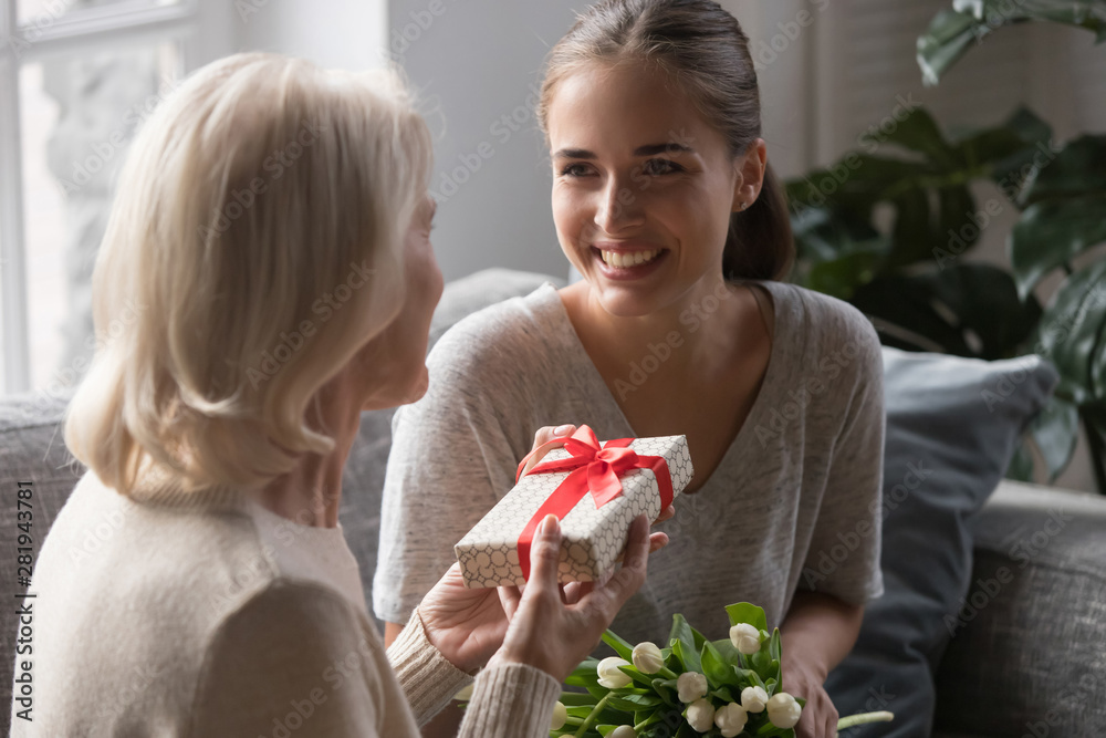 Fototapeta Middle aged mother receiving from grown up daughter gift box