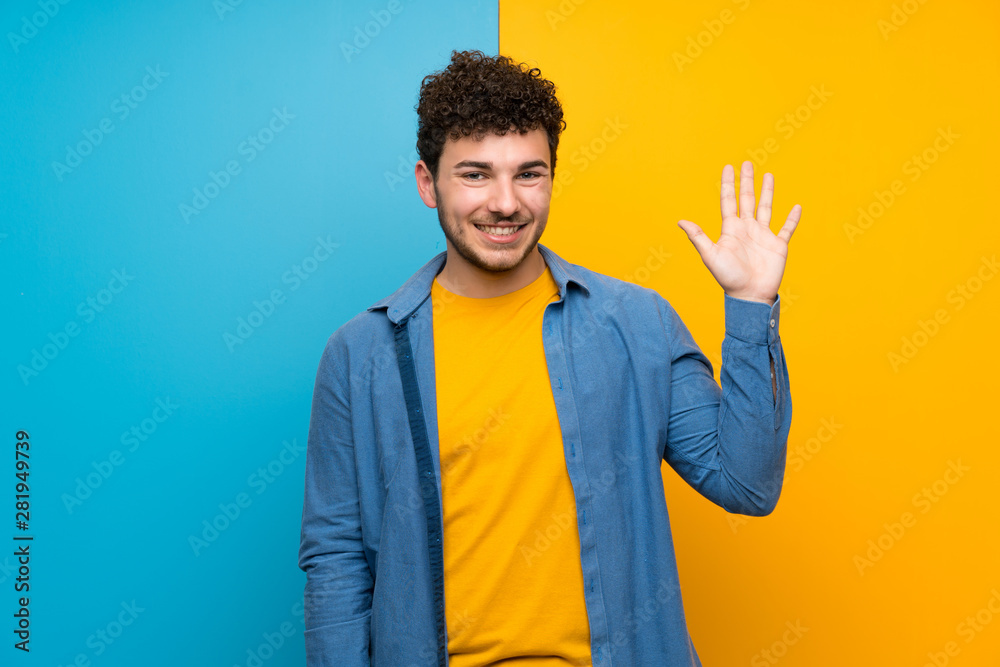 Fototapety, obrazy: Man with curly hair over colorful wall saluting with hand with happy expression
