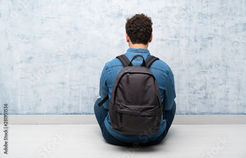 Obraz Young man sitting on the floor with backpack - fototapety do salonu