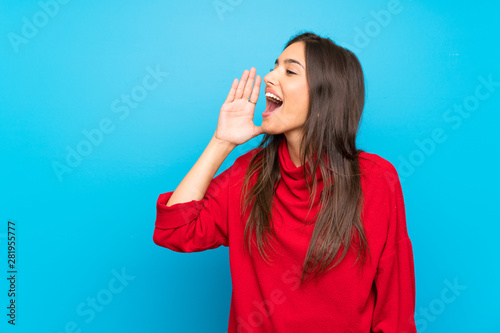 Young woman with red sweater over isolated blue background shouting with mouth w Wallpaper Mural