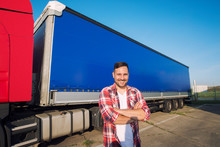 Truck Driver Occupation. Portrait Of Middle Aged Caucasian Trucker With Arms Crossed Standing By Truck Trailer Ready For Driving. Transportation Service.