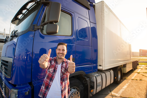 Portrait of happy smiling middle aged truck driver standing by his truck and holding thumbs up. Successful transportation service.