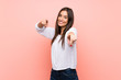 Young woman over isolated pink background points finger at you while smiling