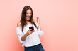 Leinwanddruck Bild - Young woman over isolated pink background with phone in victory position