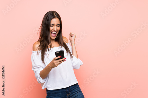 Young woman over isolated pink background with phone in victory position - 281956741