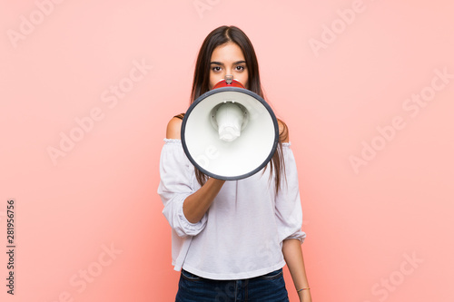 Young woman over isolated pink background shouting through a megaphone Wallpaper Mural