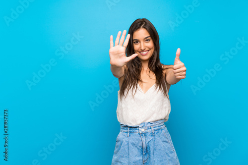 Young woman over isolated blue background counting six with fingers Poster Mural XXL