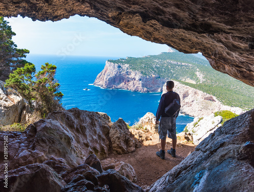 Photo Hiker with backpack by a cave in Capo Caccia