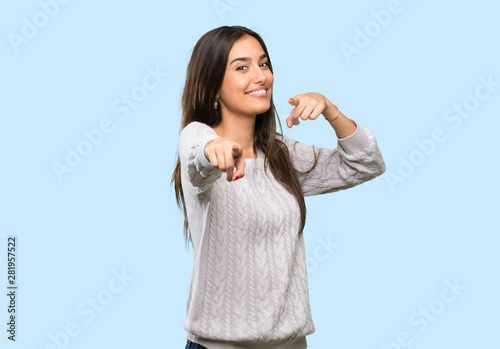 Fotomural  Young hispanic brunette woman points finger at you while smiling over isolated b