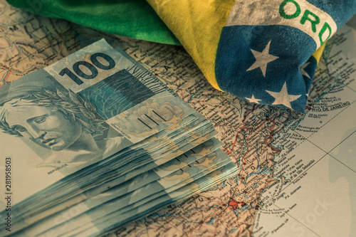 Brazilian money, 100 reais banknotes on the map of Brazil with a fragment of the Tableau sur Toile