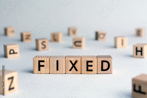 Fotomural Fixed - word from wooden blocks with letters, fixed interest rates or costs  con
