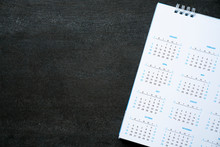Close Up Of Calendar On The Black Table, Planning For Business Meeting Or Travel Planning Concept