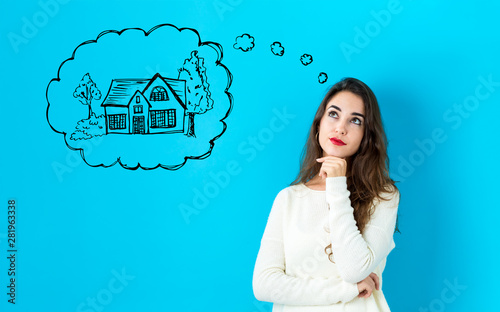 Fototapeta Dreaming of new home with young woman in a thoughtful face obraz