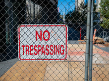 No Trespassing Sign Behind Fence Wire In Front Of Urban Construction