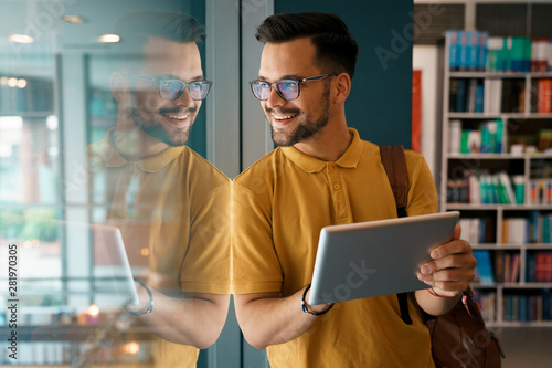 Young happy college man using digital tablet at the library - Stock Photo Canvas Print