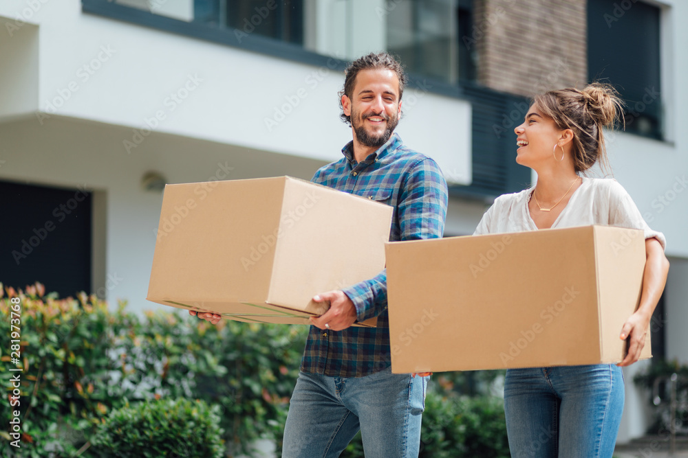 Fototapety, obrazy: Young couple carrying boxes, moving into a new apartment