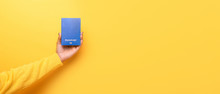 Blue Passport In Hand Over Yellow Background, Panoramic Mock Up, World Travel Concept