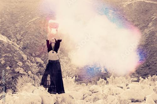 Fototapeta Priestess woman holding magic potion smoking above her head in the wilderness.  obraz