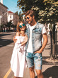 Leinwandbild Motiv Smiling beautiful girl and her handsome boyfriend walking in the street. Woman in casual summer dress and man in jeans clothes. Happy cheerful couple family having fun in sunglasses
