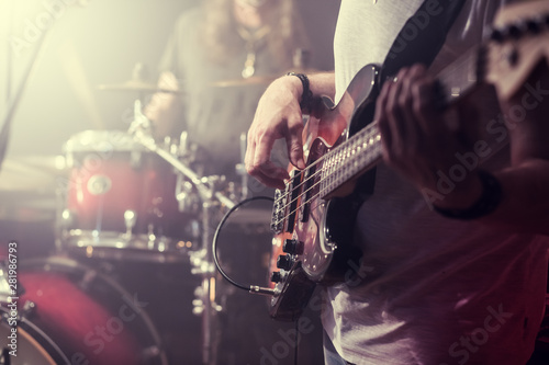 The guitarist plays the electric guitar close-up during the concert. - 281986793