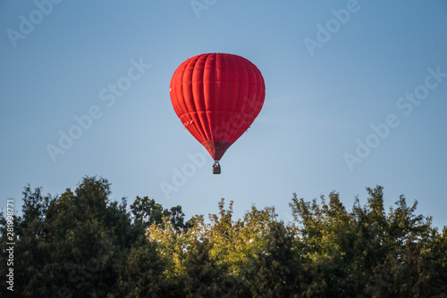 Montgolfière / Dirigeable Red hot air balloon in the sky above the trees