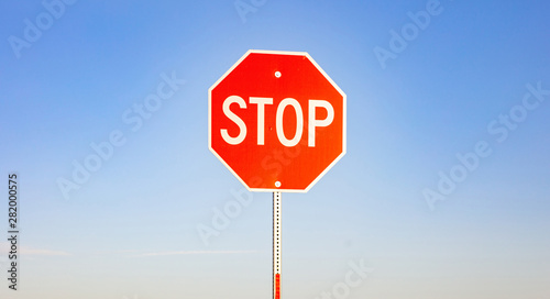 Fotomural  Stop sign against blue sky background. Sunny spring day