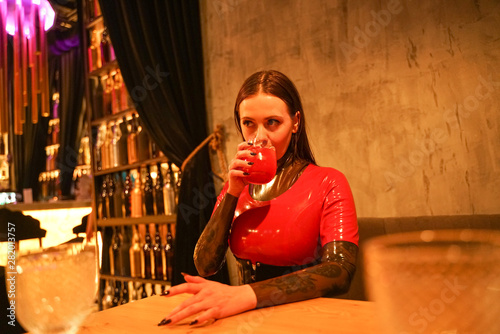 Obraz na plátne brave girl in latex walks in public and shows her exhibitionism