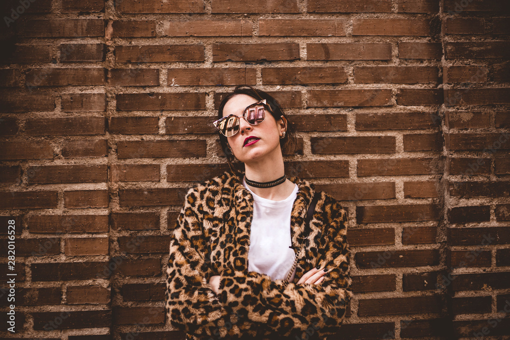 Fototapeta Stylish portrait of young serious woman with crossed arms wearing trendy leopartd print faux fur coat, fashion sunglasses, posing on red brick wall texture grunge background